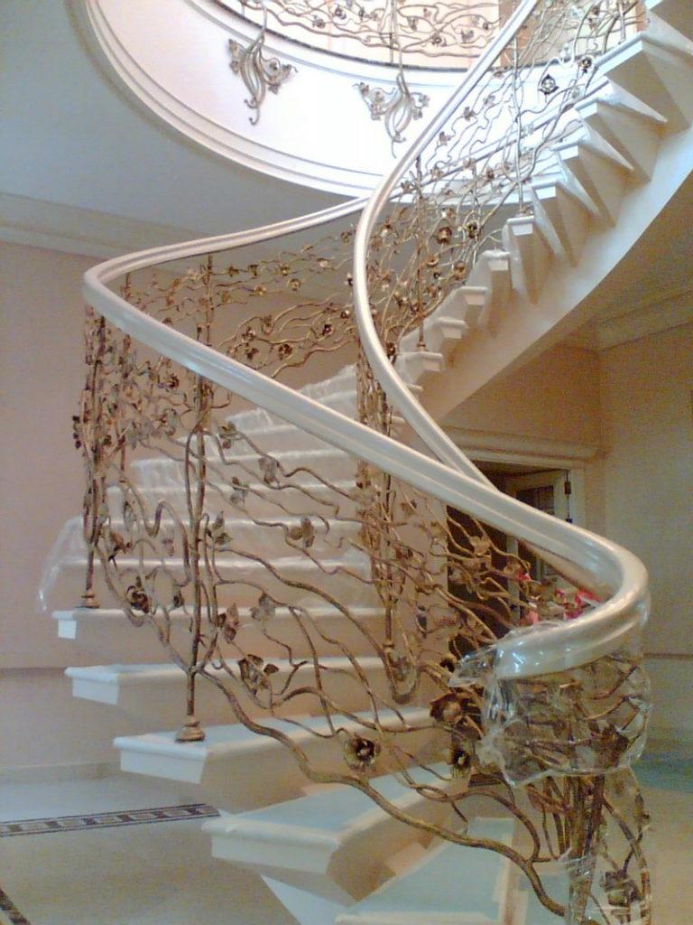 Винтовая лестница с мраморными ступенями и элементами ковки.